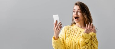panoramic shot of shocked girl showing wow gesture during video chat on smartphone isolated on grey