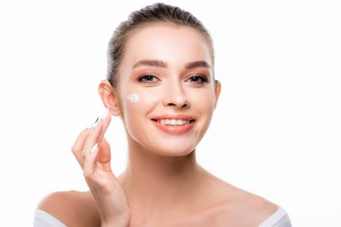 attractive, smiling woman applying cosmetic cream on face and looking at camera isolated on white