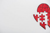 top view of drawn red heart shape jigsaw isolated on white with copy space