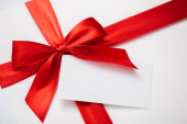 blank card near red ribbon with satin bow on white