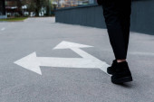 Photo cropped view of woman walking near directional arrows on asphalt