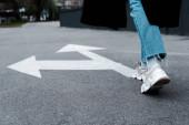 cropped view of woman in jeans walking near directional arrows on asphalt
