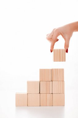 cropped view of woman putting wooden cube on white