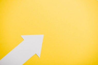 top view of directional arrow isolated on yellow with copy space