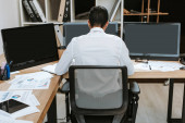 Photo back view of bi-racial trader sitting at table in office
