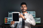 Photo smiling bi-racial trader holding digital tablet and computers with graphs on background