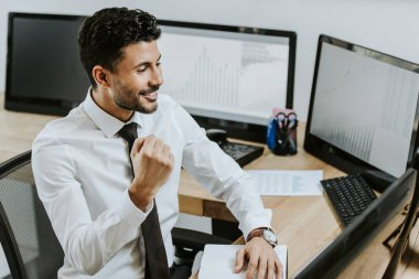 High angle view of bi-racial trader showing yes gesture and looking at computer stock vector