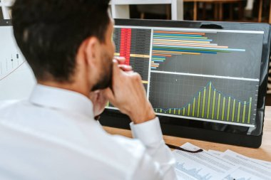 Selective focus of bi-racial trader looking at computer with graphs stock vector
