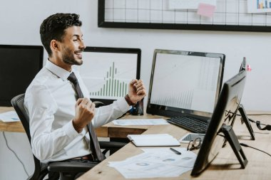 Side view of smiling bi-racial trader showing yes gesture and looking at computer stock vector