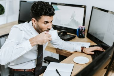High angle view of bi-racial trader drinking coffee and looking at computer stock vector