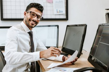 Smiling bi-racial trader holding paper and looking at camera stock vector