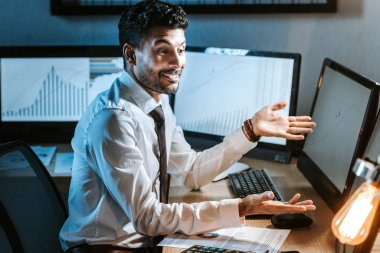Smiling bi-racial trader looking at computer with graphs in office stock vector