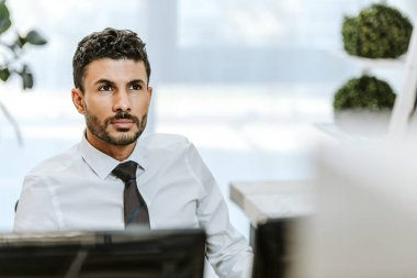 Selective focus of handsome bi-racial trader looking away in office stock vector