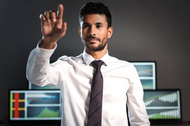 Selective focus of bi-racial trader pointing with finger and computers on background stock vector