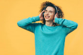 smiling curly teenager listening music in headphones with closed eyes isolated on yellow