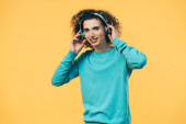 smiling curly teenager listening music in headphones isolated on yellow