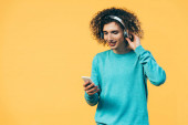 smiling curly teenager using smartphone and listening music in headphones isolated on yellow