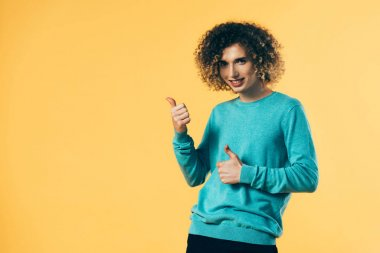 happy curly teenager showing thumbs up isolated on yellow
