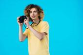 Fotografie Lächelnder, lockiger Teenager beim Fotografieren auf Filmkamera isoliert auf blauem Grund
