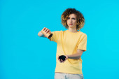 sad curly teenager flipping over empty paper cup isolated on blue