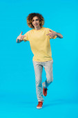 curly teenager pointing with fingers at himself isolated on blue