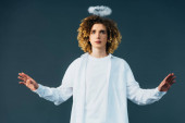 curly teenager in angel costume with halo above head and outstretched hands isolated on green