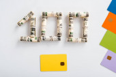 Photo top view of one hundred dollar banknotes in cash rolls near colorful credit card templates on white