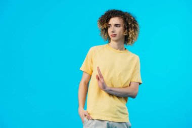 confused curly teenager with hand in pocket showing stop gesture isolated on blue