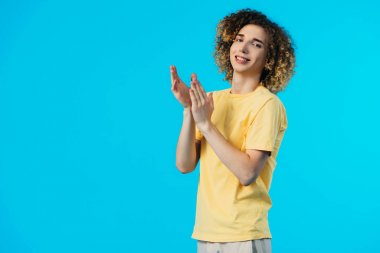 smiling curly teenager applauding isolated on blue