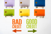 top view of credit card templates near cash rolls with dollar banknotes and letters on white