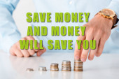 cropped view of man touching stack of coins near save money and money will save you letters on white