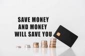 hromádky stříbrných a zlatých mincí v blízkosti šablony kreditní karty a ušetřit peníze a peníze vám ušetří dopisy na bílé