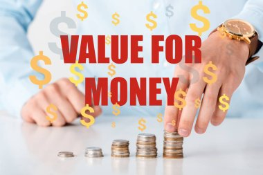 Cropped view of man touching stack of coins near value of money letters and dollar signs on white stock vector