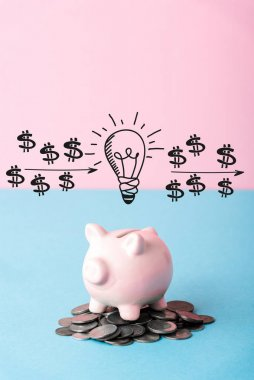 silver coins near piggy bank and light bulb on blue and pink