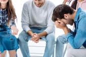 trauriger Mann sitzt auf Stuhl neben Selbsthilfegruppe isoliert auf weißem Grund