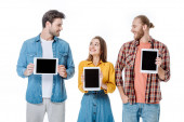 usmívající se tři mladí přátelé držící digitální tablety s prázdnými obrazovkami izolovanými na bílém