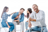 selective focus of happy man showing thumbs up while sitting on chair near multicultural support group isolated on white