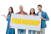 happy multicultural friends holding placard with yellow friendship lettering isolated on white
