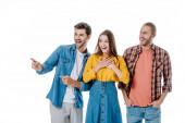 tři mladí přátelé se smějí a ukazují prstem izolovaným na bílém