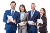 mosolygó multikulturális üzletemberek öltönyben digitális tabletta elszigetelt fehér