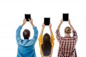 zpět pohled tří mladých přátel držících digitální tablety s prázdnými obrazovkami izolovanými na bílém