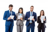 multikulturális üzletemberek öltönyben digitális táblagépet használnak, fehér alapon izolálva