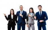 Lächelnde multikulturelle Geschäftsleute in Anzügen, die mit den Fingern zur Seite zeigen