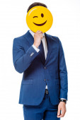KYIV, UKRAINE - AUGUST 12, 2019: businessman in blue suit holding winking smiley in front of face isolated on white