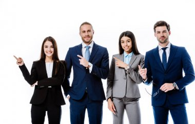 smiling multicultural business people in suits pointing with fingers aside isolated on white