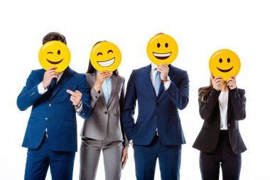 KYIV, UKRAINE - AUGUST 12, 2019: multicultural business people in suits holding emoji in front of faces isolated on white stock vector