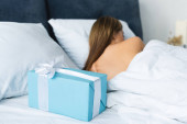 back view of woman sleeping in bed near gift box