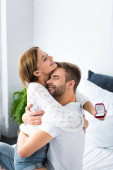 handsome man hugging smiling woman with engagement ring
