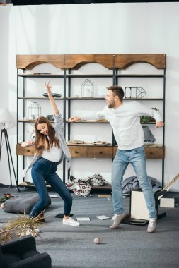 smiling woman and handsome man dancing at robbed home