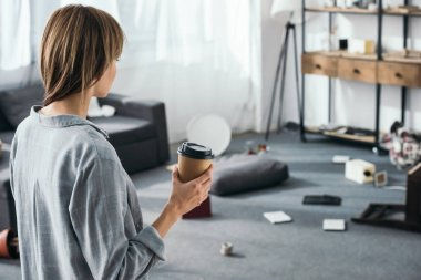 woman holding paper cup and looking at robbed apartment